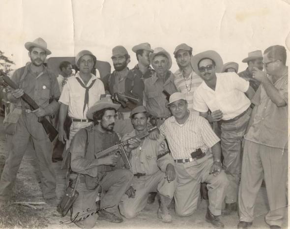 En la foto con la metralleta, agachado, René Vallina Mendoza