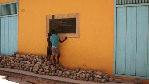 Niños observan placa en momentos de remozamiento de edificio de  valor patrimonial en La Habana Vieja