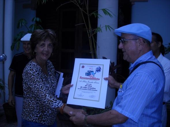 Mirtha González recibe diploma de manos de Oscar Viñas, presidente de la filial de Radio, cine y TV de la UNEAC camagüeyana